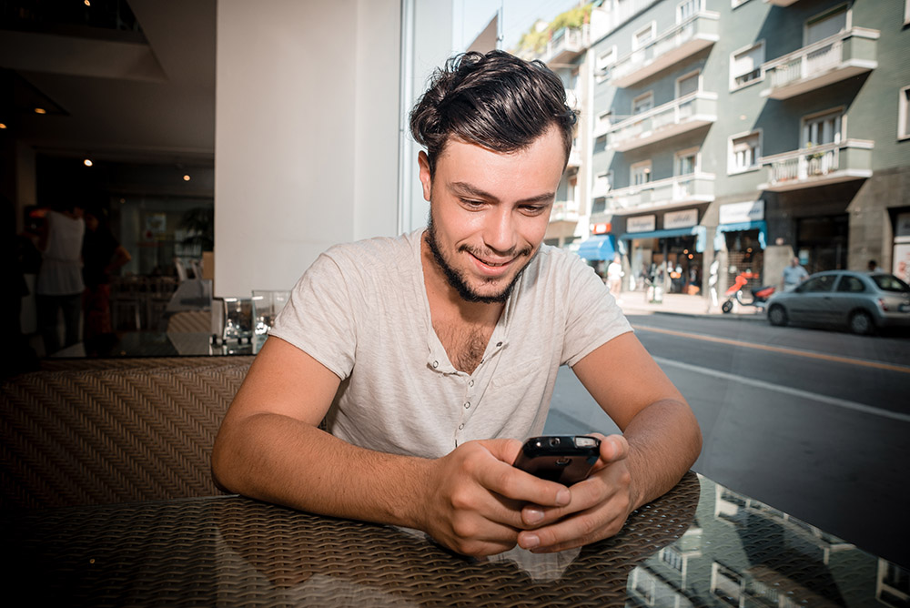 cute-guy-bar-playing-mobile-phone